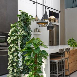 Mittelgroße Moderne Wohnküche ohne Kamin mit weißer Wandfarbe, Betonboden und grauem Boden in Berlin