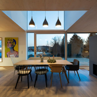 Große Moderne Wohnküche mit weißer Wandfarbe, hellem Holzboden, Tunnelkamin, verputzter Kaminumrandung und beigem Boden in Nürnberg