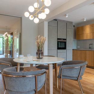 Mittelgroße Moderne Wohnküche mit grauer Wandfarbe und braunem Boden in Hannover