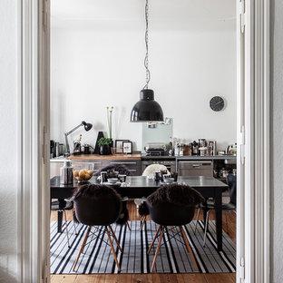 Geschlossenes, Mittelgroßes Industrial Esszimmer ohne Kamin mit weißer Wandfarbe, braunem Holzboden und braunem Boden