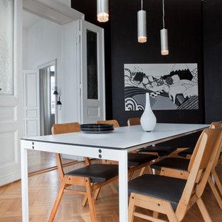 Idées déco pour une salle à manger scandinave fermée et de taille moyenne avec un mur noir et un sol en bois clair.