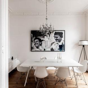 Geschlossenes Nordisches Esszimmer mit weißer Wandfarbe, braunem Holzboden und braunem Boden in Hamburg