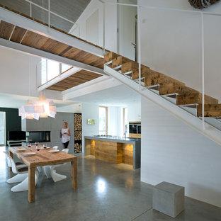 Exemple d'une grand salle à manger ouverte sur la cuisine tendance avec un mur blanc, béton au sol, une cheminée double-face, un manteau de cheminée en béton et un sol gris.