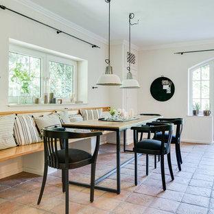 Idee per una sala da pranzo mediterranea chiusa e di medie dimensioni con pareti bianche, pavimento in terracotta, nessun camino e pavimento rosso