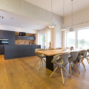 Große Moderne Wohnküche ohne Kamin mit weißer Wandfarbe, braunem Holzboden und braunem Boden in Nürnberg