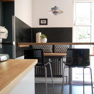 Kleine Moderne Wohnküche ohne Kamin mit weißer Wandfarbe und grauem Boden in Berlin