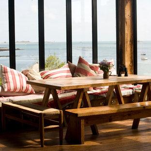Exemple d'une salle à manger ouverte sur le salon bord de mer de taille moyenne avec un mur marron, un sol en bois brun et aucune cheminée.
