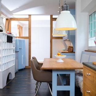 Mittelgroße Nordische Wohnküche mit dunklem Holzboden, schwarzem Boden, weißer Wandfarbe, Kaminofen und gefliestem Kaminsims in Köln