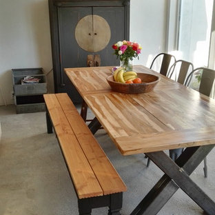 Photo of a shabby-chic style dining room in Cologne with white walls and concrete floors.
