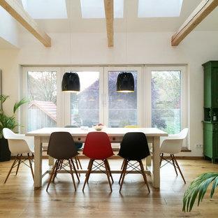 Diseño de comedor actual, grande, abierto, con paredes blancas, suelo de madera pintada y suelo marrón