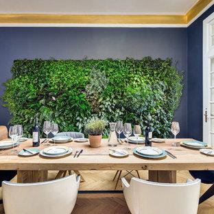 Idee per una grande sala da pranzo aperta verso il soggiorno eclettica con pareti blu e parquet chiaro