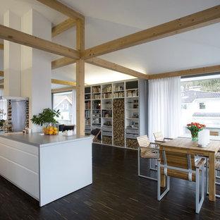 Offenes Modernes Esszimmer mit braunem Boden, weißer Wandfarbe und dunklem Holzboden in München