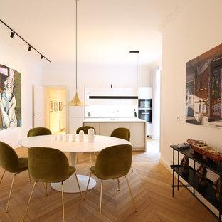 Große Moderne Wohnküche ohne Kamin mit beigem Boden, weißer Wandfarbe und hellem Holzboden in Berlin