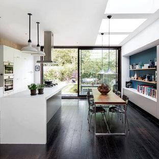 Mittelgroße Moderne Wohnküche ohne Kamin mit weißer Wandfarbe, dunklem Holzboden und braunem Boden in Hamburg