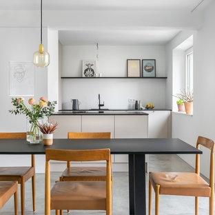 Moderne Wohnküche mit weißer Wandfarbe und grauem Boden in München