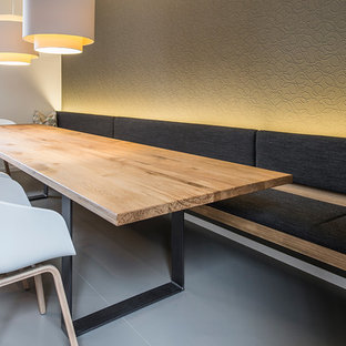Large contemporary dining room in Berlin with brown walls, concrete floors and no fireplace.