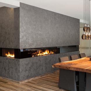 Imagen de comedor de cocina contemporáneo, de tamaño medio, con paredes blancas, suelo de madera oscura, chimenea lineal y marco de chimenea de yeso