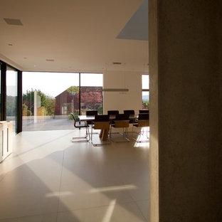 Immagine di una grande sala da pranzo aperta verso il soggiorno contemporanea con pareti bianche, pavimento in ardesia e pavimento beige