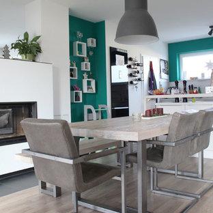 Cette photo montre une salle à manger ouverte sur la cuisine scandinave avec un mur blanc, un sol en vinyl, un sol marron et une cheminée double-face.