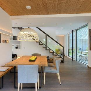 Foto di una sala da pranzo aperta verso il soggiorno minimal con pareti bianche, parquet scuro, pavimento marrone e soffitto in legno