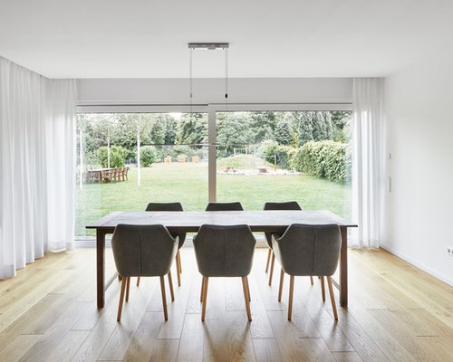 Inspiration for a mid sized modern dining room in essen with white walls light