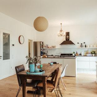 Große Stilmix Wohnküche ohne Kamin mit weißer Wandfarbe, hellem Holzboden und beigem Boden in Köln