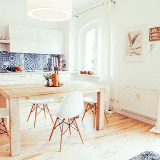 Geräumige Moderne Wohnküche mit weißer Wandfarbe und hellem Holzboden in Berlin