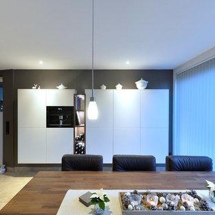 Foto di una sala da pranzo aperta verso il soggiorno design di medie dimensioni con pareti nere, pavimento con piastrelle in ceramica, nessun camino e pavimento beige