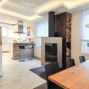 Immagine di una grande sala da pranzo aperta verso il soggiorno minimal con pareti bianche, parquet chiaro, camino sospeso, cornice del camino in metallo e pavimento beige