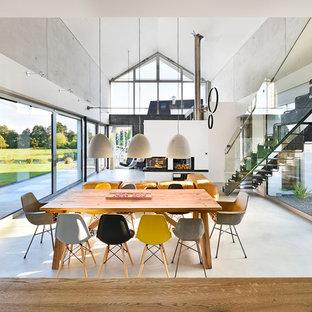 Modelo de comedor actual, extra grande, abierto, con paredes grises, suelo de cemento, chimenea de esquina, marco de chimenea de yeso y suelo gris