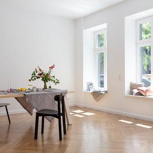Mittelgroßes Skandinavisches Esszimmer ohne Kamin mit braunem Holzboden, weißer Wandfarbe und beigem Boden in Berlin
