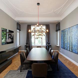 Aménagement d'une salle à manger contemporaine fermée et de taille moyenne avec un mur gris, un sol marron et un sol en bois clair.