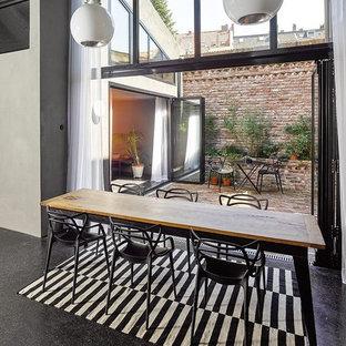 Immagine di una sala da pranzo aperta verso il soggiorno industriale di medie dimensioni con pareti bianche, pavimento in linoleum, nessun camino e pavimento nero