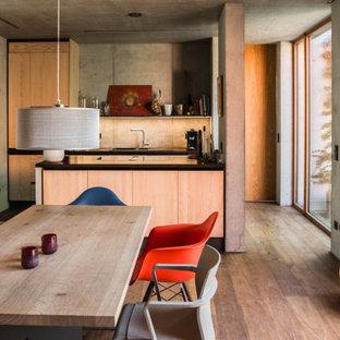 Moderne Wohnküche mit grauer Wandfarbe, dunklem Holzboden und braunem Boden in Sonstige