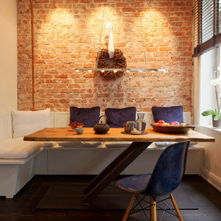 Modelo de comedor de cocina industrial, extra grande, sin chimenea, con paredes beige, suelo de madera oscura, marco de chimenea de ladrillo y suelo marrón