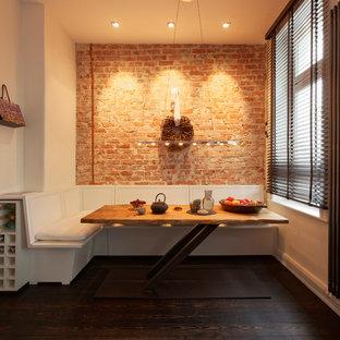 Modelo de comedor de cocina actual, extra grande, sin chimenea, con paredes blancas, suelo de madera oscura, marco de chimenea de ladrillo y suelo marrón