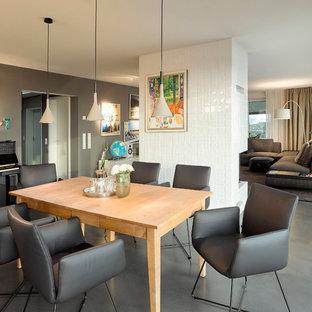 Idee per una grande sala da pranzo aperta verso il soggiorno contemporanea con pareti marroni, pavimento in linoleum, stufa a legna, cornice del camino piastrellata e pavimento grigio