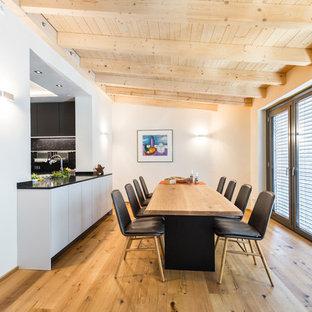 Mittelgroße Moderne Wohnküche mit weißer Wandfarbe, hellem Holzboden und braunem Boden in Leipzig