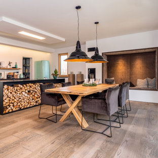Foto di una grande sala da pranzo aperta verso il soggiorno american style con pareti bianche, pavimento in legno massello medio e pavimento grigio