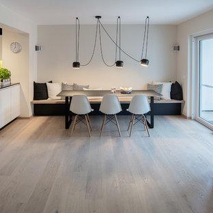 Ispirazione per una sala da pranzo aperta verso la cucina minimal di medie dimensioni con pareti bianche, parquet chiaro, nessun camino e pavimento blu