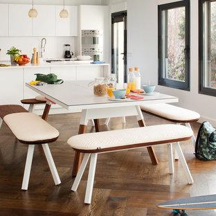 Große Moderne Wohnküche ohne Kamin mit weißer Wandfarbe, dunklem Holzboden und braunem Boden in Berlin