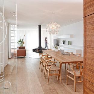 Réalisation d'une salle à manger ouverte sur le salon design de taille moyenne avec un mur blanc, un sol en bois clair et cheminée suspendue.