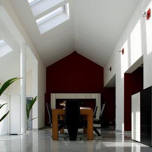 Ejemplo de comedor minimalista, de tamaño medio, abierto, con paredes rojas, suelo de mármol, chimenea tradicional, marco de chimenea de yeso y suelo gris