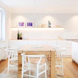 Nordische Wohnküche ohne Kamin mit weißer Wandfarbe, braunem Holzboden und braunem Boden in München
