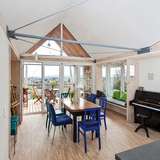 Immagine di una grande sala da pranzo minimal chiusa con pareti bianche, pavimento in bambù e pavimento beige