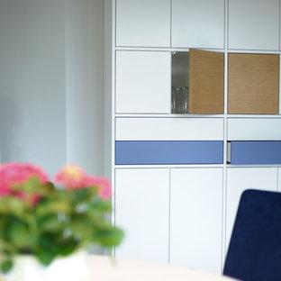 Immagine di un'ampia sala da pranzo aperta verso il soggiorno etnica con pareti grigie, pavimento in linoleum, stufa a legna, cornice del camino in cemento e pavimento beige