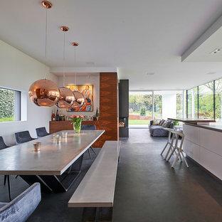 Große Moderne Wohnküche ohne Kamin mit weißer Wandfarbe, Betonboden und schwarzem Boden