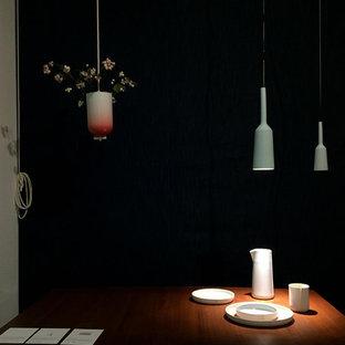 Ejemplo de comedor escandinavo, grande, abierto, con paredes negras, suelo de madera en tonos medios, estufa de leña, marco de chimenea de hormigón y suelo marrón