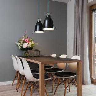 Réalisation d'une petite salle à manger nordique avec un mur gris et un sol en bois clair.
