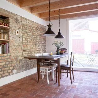 Imagen de comedor de cocina rústico, grande, sin chimenea, con suelo de baldosas de terracota y suelo rojo